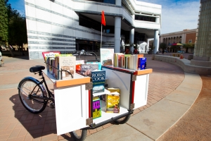 Photo of Pima County Public Libraries' (PCPL) first Book Bike on January 30, 2012 at the Joel D. Valdez Main Library.  The modified cargo bike, made by Haley Tricycles in Philadelphia, is outfitted with book shelves.  Donated books will be given away during appearances. Photo provided by PCPL.